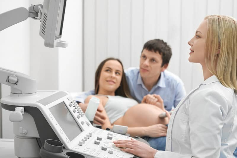A husband is at the doctor's with his pregnant wife, who is getting an ultrasound. The husband is doing his best to be supportive and helpful during the pregnancy.