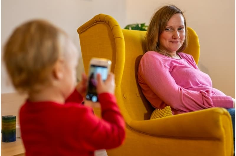 A pregnant mom is getting her picture taken by her toddler son.