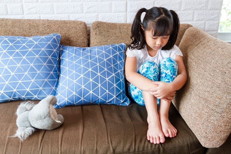 A toddler girl is sitting alone on the sofa, sad after she had been spanked.