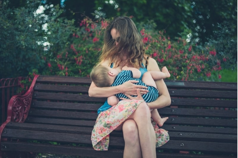 A young mom is breastfeeding her baby boy on a park bench.