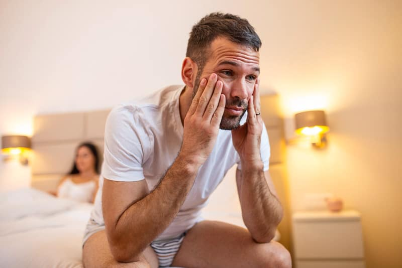A frustrated husband is sitting on the bed, away from his wife, who is pregnant and needing his support.