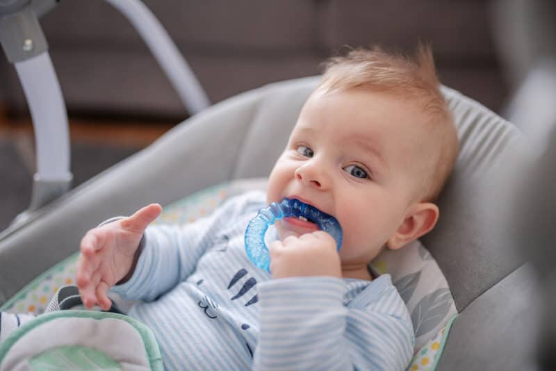 An infant boy with swollen lymph nodes is also laying down and chewing on a teether, because of his current teething phase.