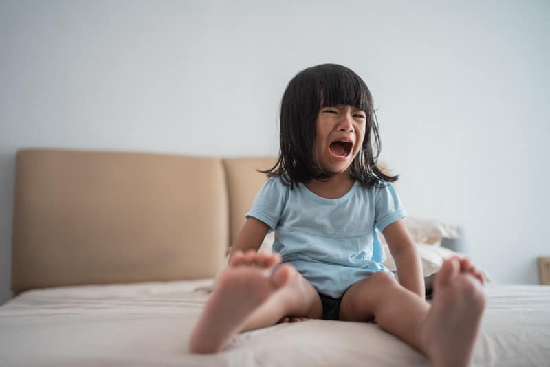 A toddler girl is crying and screaming on her bed. She's having a temper tantrum.