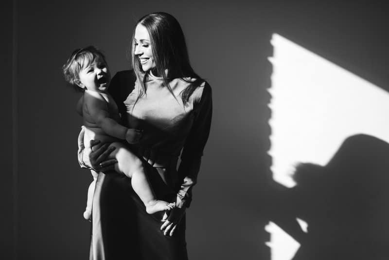 A young mom is happy and holding her infant boy.