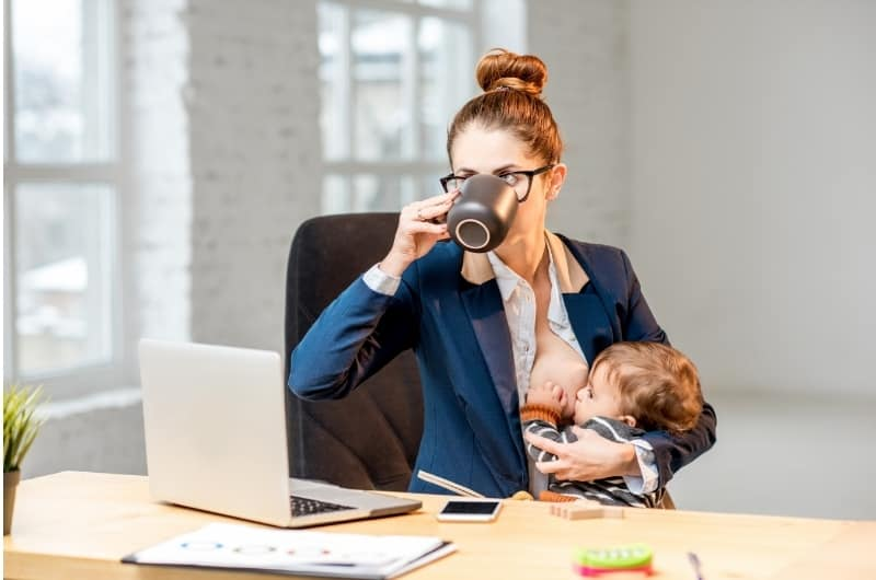 A working mom is breastfeeding her infant boy.