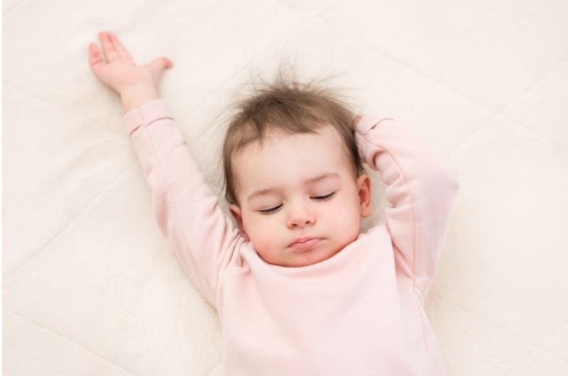 A toddler girl is sleeping on the rug on the floor, instead of her crib.