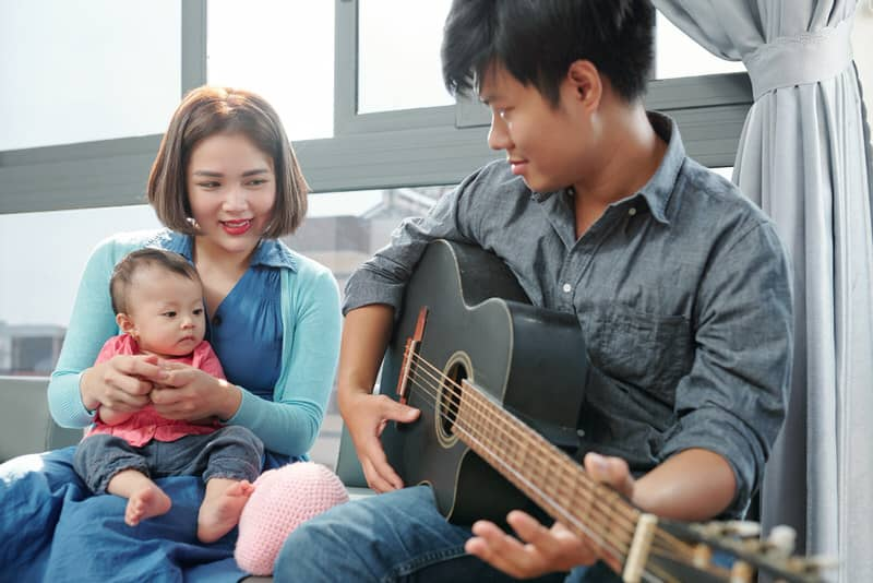 A young family of 3 are bonding, dad is playing the guitar to mom and baby, who are happy and listening along.