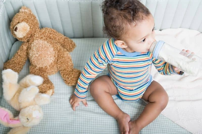 An infant baby boy is sitting in his crib, drinking milk from a bottle.