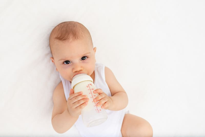 An infant baby boy is holding his bottle and drinking formula milk by himself.