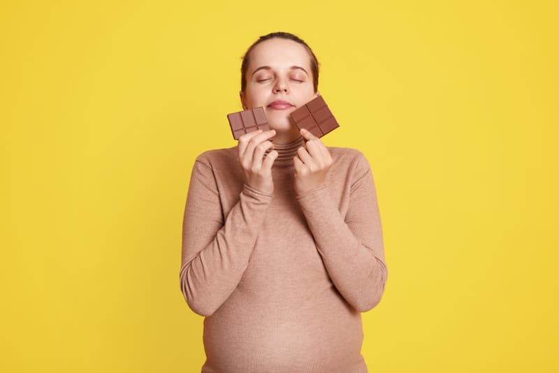 A new mom is about to eat some chocolate. She needs to be aware of the caffeine content since she is still breastfeeding.