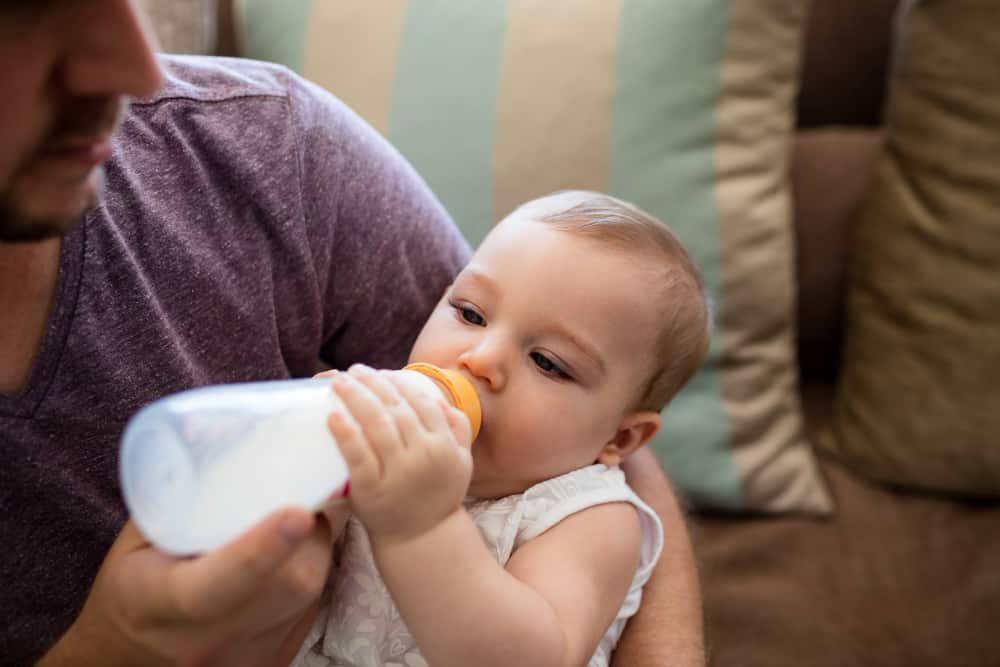 A dad is formula feeding his baby daughter.