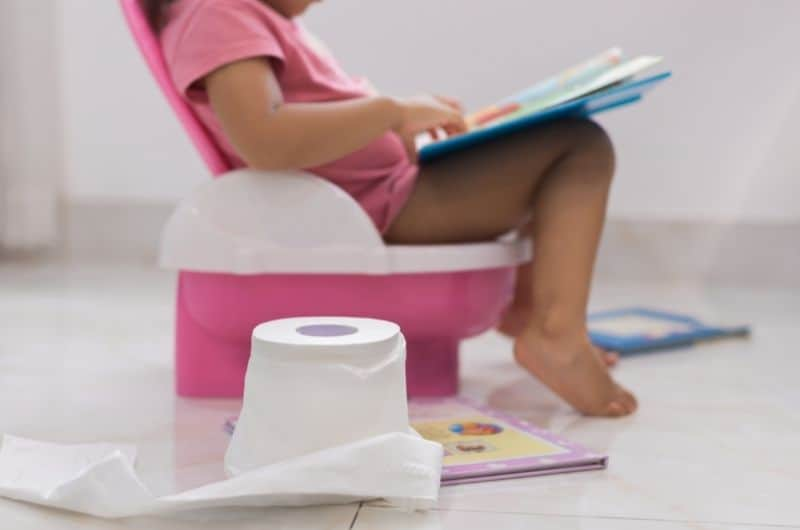 A toddler girl is sitting on the potty and reading a book.