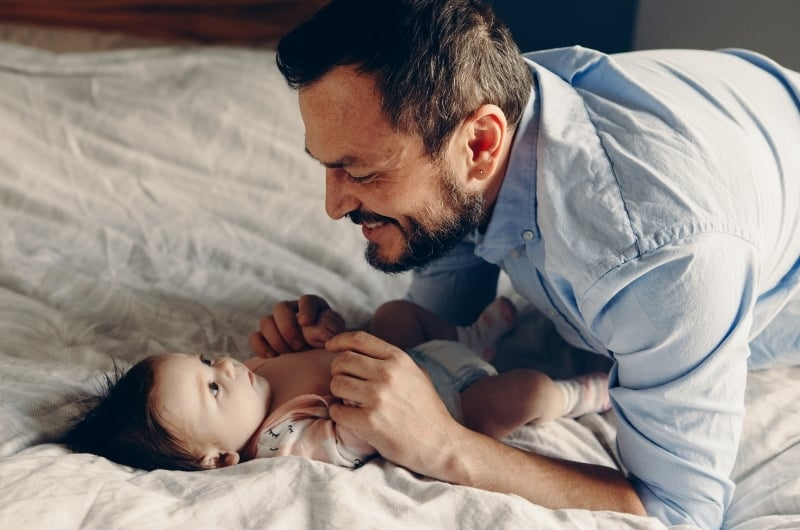 Dad is talking to his infant son, trying to help him talk back, to get to his speech development milestone.