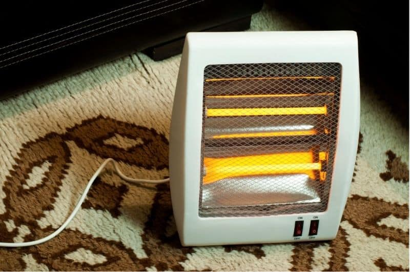 A space heater is placed on a carpeted floor and is turned on and heating the nearby space around it.