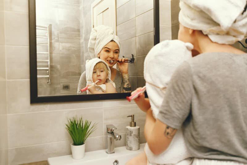 Mother and son are bonding when mom is teaching son how to brush his teeth.