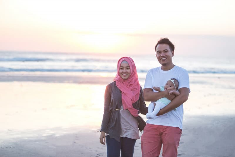 A young couple are at the beach with their newborn baby.