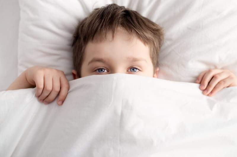 A toddler boy is sleeping in his bed, with his face covered.