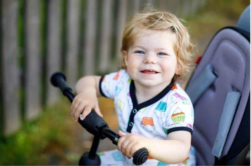 A toddler is smiling while sitting on her stroller.