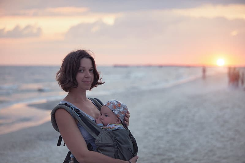 A young mom is holding her newborn baby in a baby carrier, while walking around at the beach.