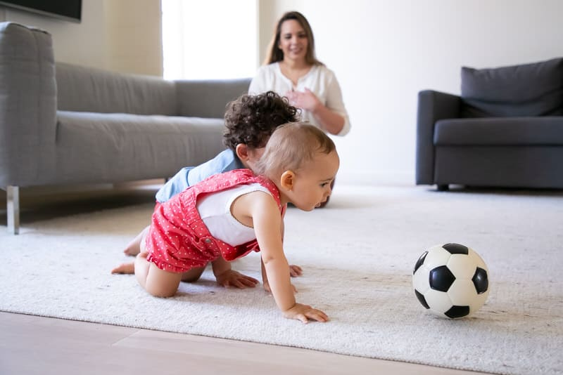Two infant babies are playing on the floor, crawling and chasing a soccer ball.
