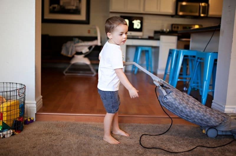 A toddler boy is vacuuming the carpet at home as a way to learn to do chores.