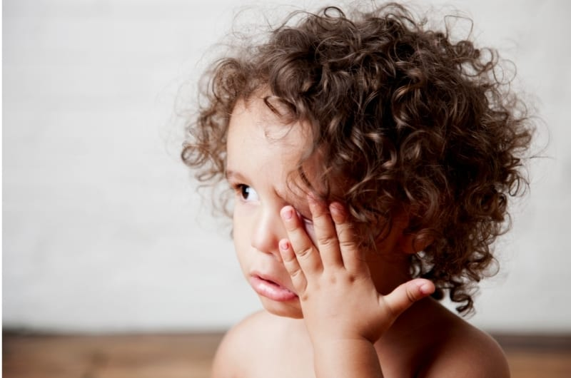 A young toddler girl is rolling her eyes and then starts rubbing one of them.