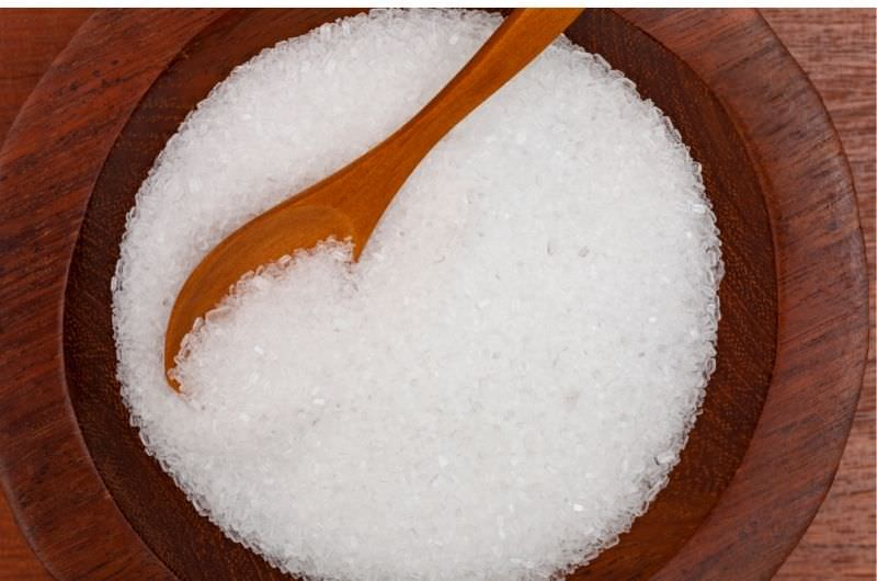 Epsom salt in a wooden bowl with a wooden spoon.