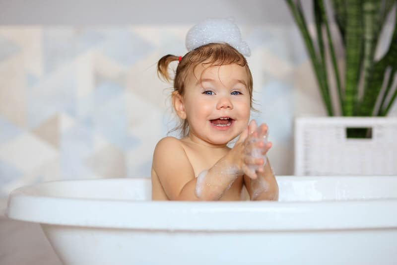 A toddler girl is happily playing in the bath tub while she's having a bath.