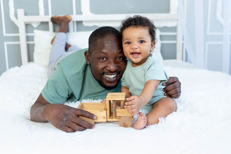 Dad and his infant daughter are hanging out and playing on the bed.