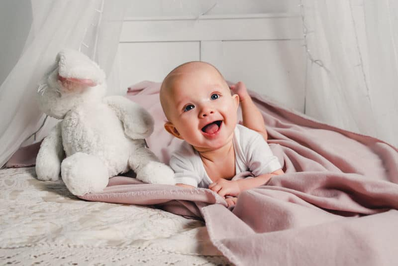 A happy infant boy is laying on his tummy on his crib blanket.