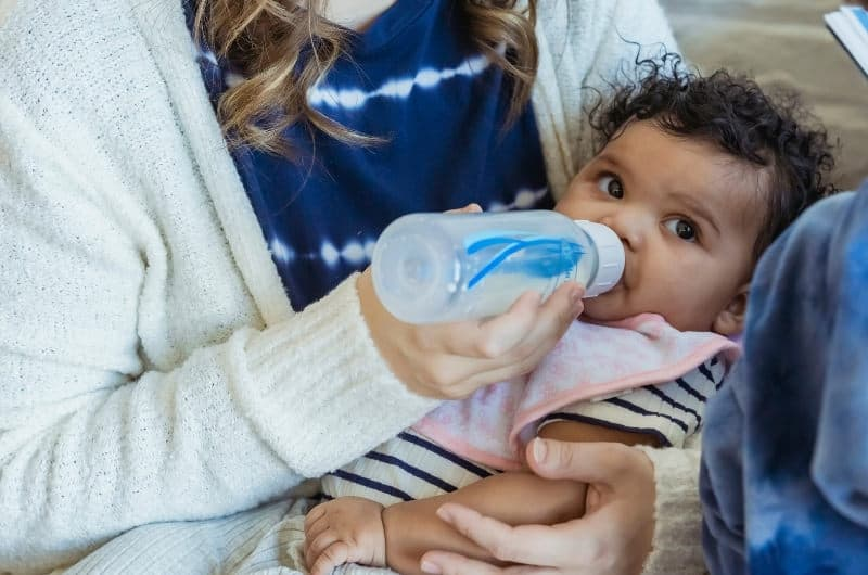 An infant girl is drinking milk from a bottle.