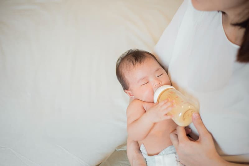 Mom is feeding her newborn son from a bottle, which contains half frozen breastmilk and half fresh breastmilk.