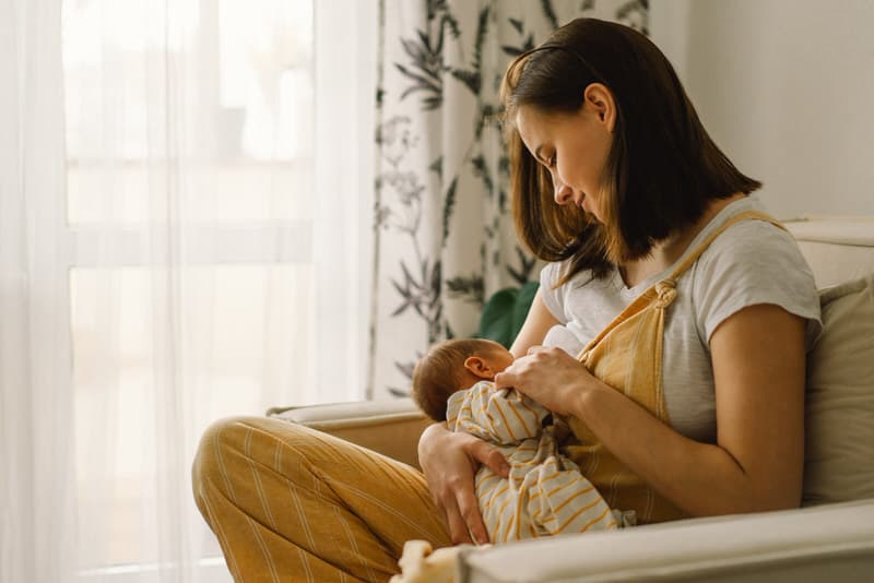 A young mom of a newborn is trying to fix her shallow latch with her baby so both can have a better breastfeeding experience.