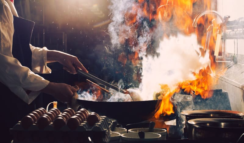 A restaurant chef is cooking with wine, and as a result, there's a small fire from the alcohol burn.