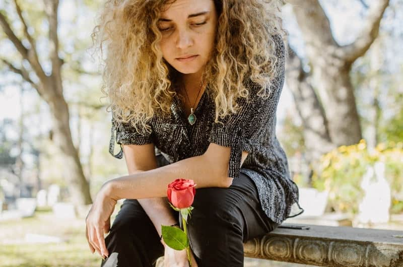 A young woman is trying to cope with her miscarriage. She has a red flower and is sitting by the tombstone dedicated to her unborn baby.