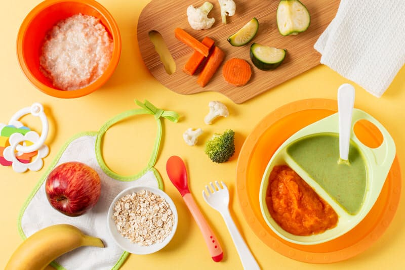 A variety of healthy food items are laid out on a table, suitable for infants to eat.
