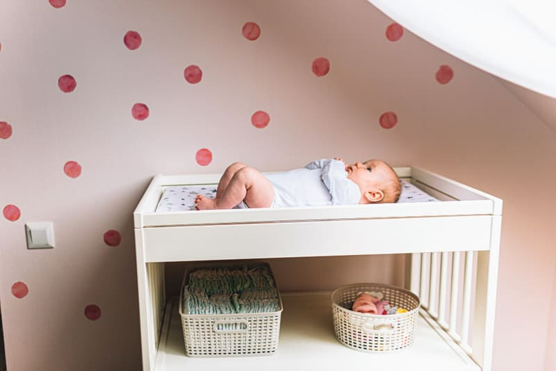 An infant boy is laying down on his diaper changing table.