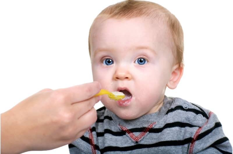 An infant boy is eating rice cereal as one of his first introductions to solid foods. Rice cereal is easy to digest and healthy.