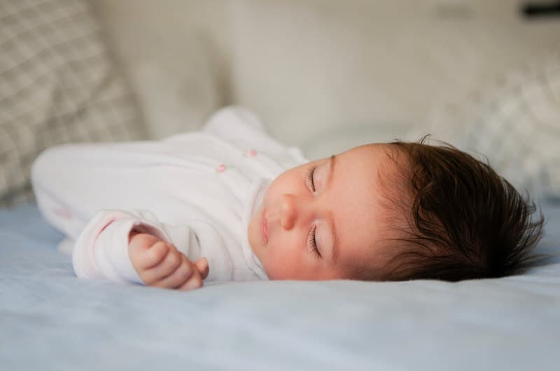 An infant baby is sleeping safely on a mattress in her crib.