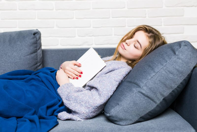 A young woman is sleeping on the sofa with her back inclined.