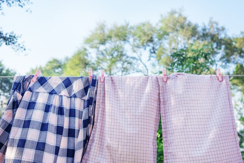 Mom is sun drying her clothes after washing them, to get newborn baby's spit-up smell out of them.