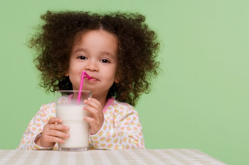 A toddler girl is drinking milk from a cup using a straw.