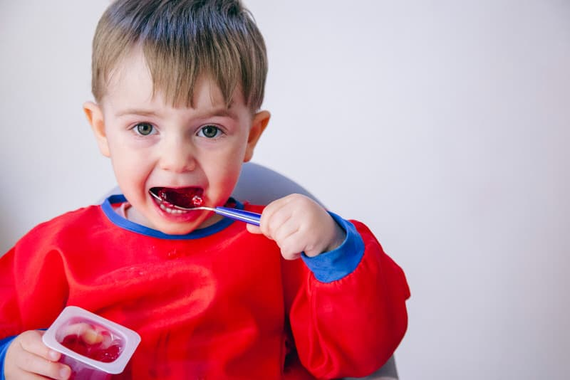 A toddler boy is happily eating his jello snack, not an ideal snack for infants or newborns.