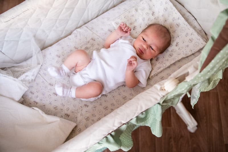 An infant boy is laying in his crib, looking around the room.