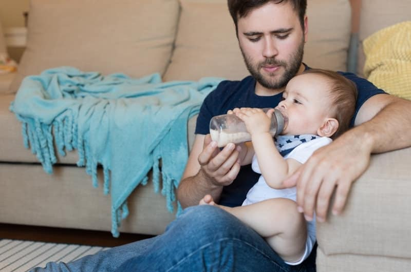 Dad is bottle feeding formula milk to his infant son.