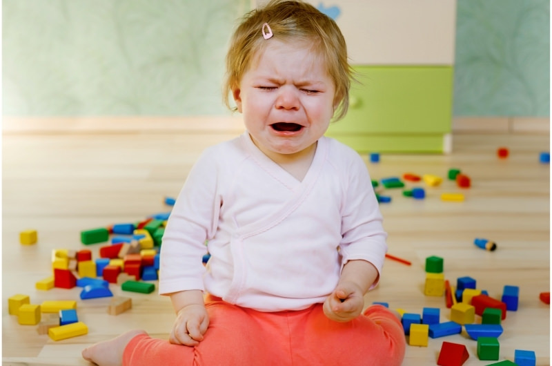 An infant girl is sitting and crying at daycare because she's new there and doesn't like the new environment change.
