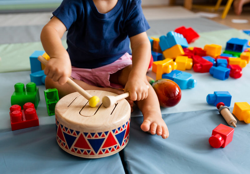 A toddler boy is playing with drums at daycare and is having too much fun to stop and go have a snack.