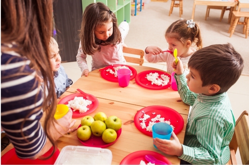 A group of toddlers are sitting together at daycare and having lunch.