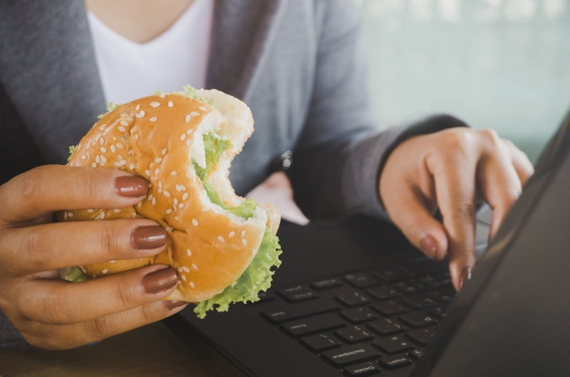 A young mom who is stressed out from her new parenting lifestyle, is eating an unhealthy burger while working on her laptop.