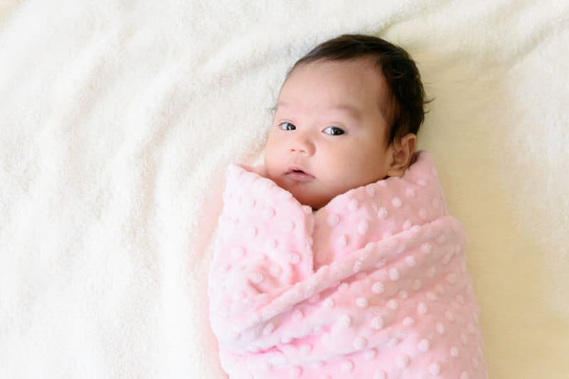 A swaddled baby is happy and comfortable.